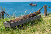 Rusty old cannon on the seashore. In the background a sailing ship.