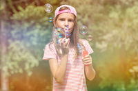 Girl playing with bubbles on sunny day