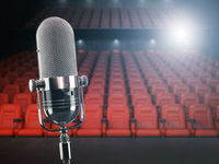 Vintage microphone on the stage of concert hall or theater with red seats and spot light.