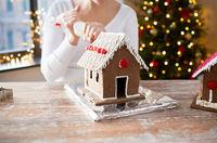 woman making gingerbread houses on christmas