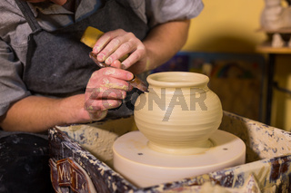 Professional potter carving pot with special tool in pottery workshop