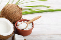 Background of coconut, coconut shell, oil in clay bowl and spoon on white wooden table