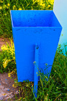 Empty Garbage Bin Painted in bright blue color in the garden