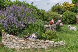 Kräutergarten in handgemachter Kräuterspirale aus Steinen - davor weisser Hund