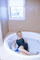 Woman wearing slip dress relaxing in the bath