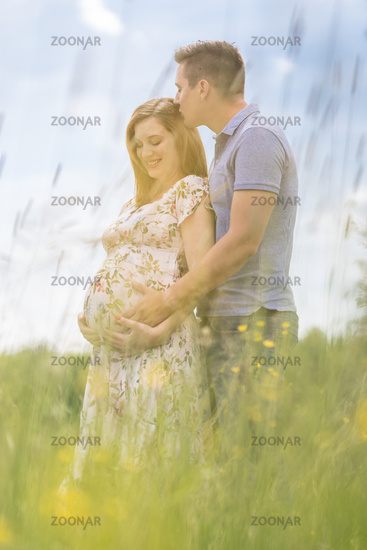 Young happy pregnant couple hugging in nature.