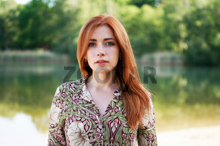 cool young woman floral pattern ummer dress standing by lake