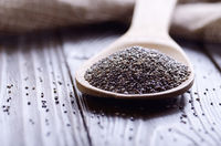 Raw Chia seeds in bamboo spatula on wooden table