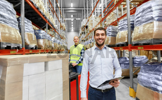 businessman and worker on forklift at warehouse