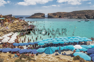 Comino Island, Malta Blue Lagoon panoramic landscape with bathers and sun umbrellas.