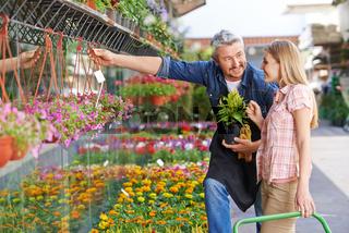 Verkäufer im Blumenladen hilft Frau
