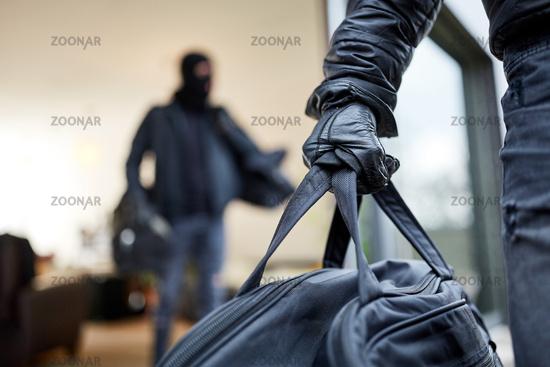 Einbrecher tragen Tasche mit Beute aus Haus