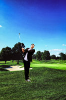 Full body shot of a man standing on a golf course
