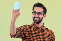 Happy young bearded Persian hipster man taking selfie