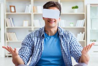 Man wearing virtual reality VR glasses meditating on floor at ho