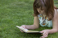 Learning, redhead girl reading a book in a park with nice green grass, nature and healthy life