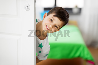 happy little boy behind door at home