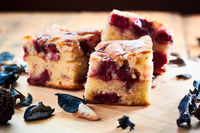 Delicious cake with cherries on wooden table