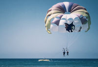 Big beautiful parachute in the air over the sea.