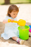 little baby girl plays with toys in sandbox