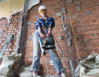 young woman in work clothes and a protective helmet stands next to a brick wall and holds a heavy ha