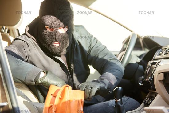 Dieb wühlt nach Auto Einbruch in Handtasche
