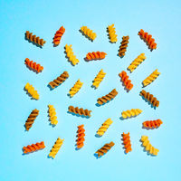 Pattern of multi-colored pasta on a blue background. Flat lay.