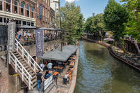 Dutch city Utrecht with shopping people and terraces along canal