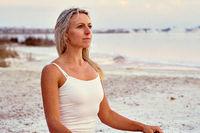 Middle aged 50s yogi woman meditating on nature