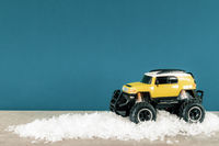 yellow SUV monster car truck toy in winter snow