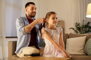 father braiding daughter hair at home