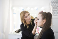 Professional make up artist doing make up in beauty salon