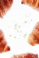 Frame of fresh homemade croissants with crumbs on a light background.