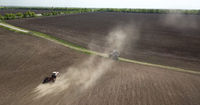 Planning works in the field, a tractor with a harrow, tillage, soil preparation for agricultural works. View from a bird's eye
