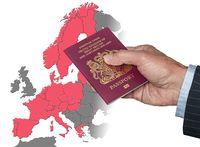 Man holding UK passport on map of EU Schengen Zone