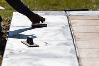 Construction Worker Smoothing Wet Cement With Hand Edger Tool