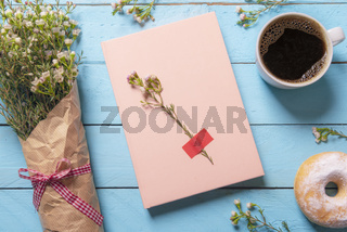 Pink notebook on a wooden table and white flowers bouquet