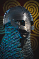 Traditional Vikings, viking helmet with chain mail on a red shield with golden shapes of sun, weapons for war