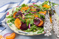 Delicious salad of arugula, tangerines and baked beets close-up.