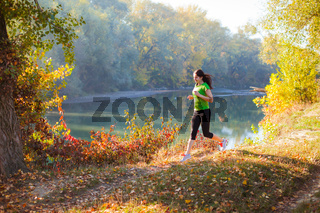 Active woman training in the autumn city park