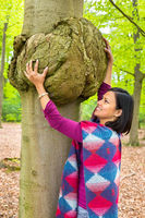 Woman holding cancerous tumor on beech tree