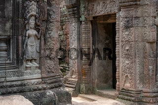 Decorated stone entrance to temple opposite statue