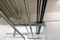 metal and plastic pipe system on the cellar ceiling of an apartment building