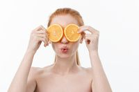 Great food for a healthy lifestyle. Beautiful young shirtless woman holding piece of orange standing against white background.