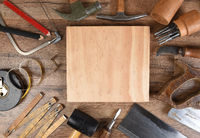 High angle closeup of a large group of tools arranged around an piece of wood, an ideal space for yo