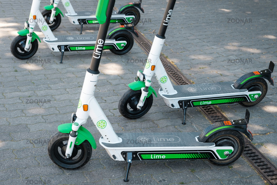 Electric scooter , escooter or e-scooter of the ride sharing company LIME on sidewalk