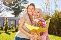 Frau schenkt ihrer Mutter einen Blumenstrauß
