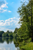 View at lake or river shore under blue cloudy sky