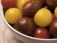 Cherry tomatoes in ceramic bowl on wooden background.