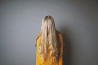 depressed young woman hiding her face behind long blond hair